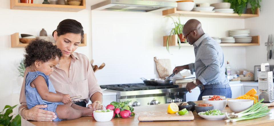 Family in Kitchen with Baby on Counter and Veggies