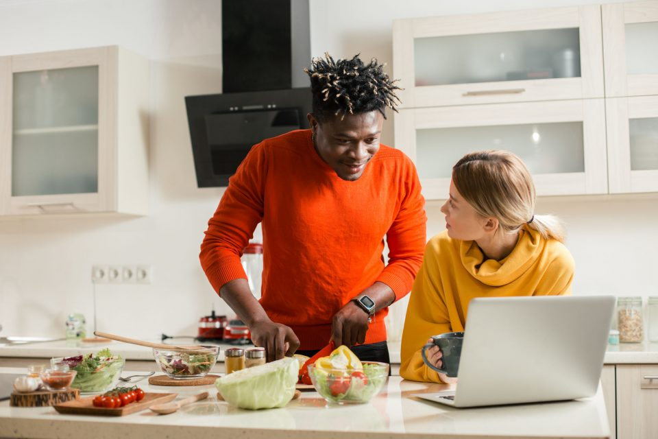 Man cutting vegetables and looking at the screen of laptop