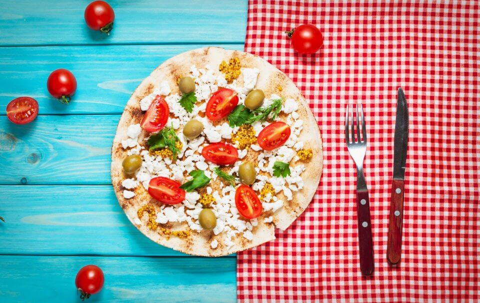 Pita with cheese, cherry tomatoes, olives and greenery on blue wooden background.