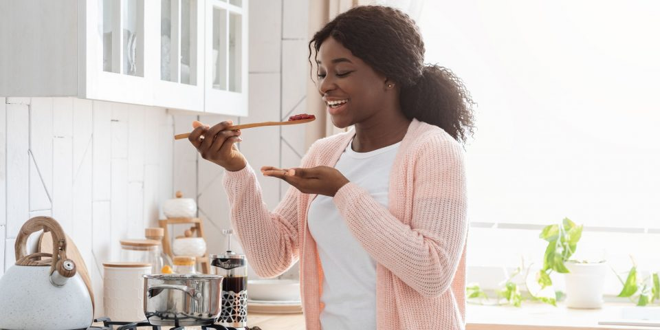 Cheerful Black Housewife Tasting Food While Cooking Healthy Lunch In Modern Kitchen